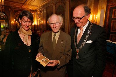 Piet Slegers geflankeerd door burgemeester de Graaf en de ontwerpster van de ring, Beate Klockmann foto - Cees Baars
